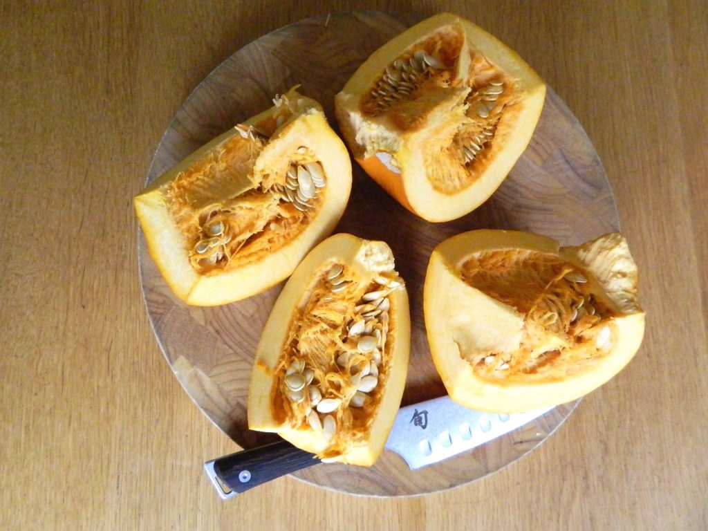 pumpkin cut in fourths and ready to be roasted for Roasted Pumpkin Soup - finestofsuppers.com