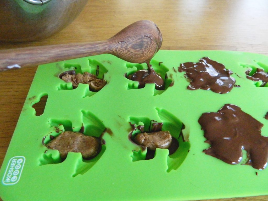 Covering filling with chocolate in Dark Chocolate Almond Butter Frogs - finestofsuppers.com